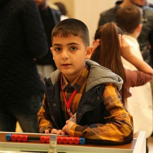 A boy waits with other young refugees, including many of from Syria and Iraq, for a Nov. 30 meeting with Pope Francis in Istanbul's Salesian Oratory.