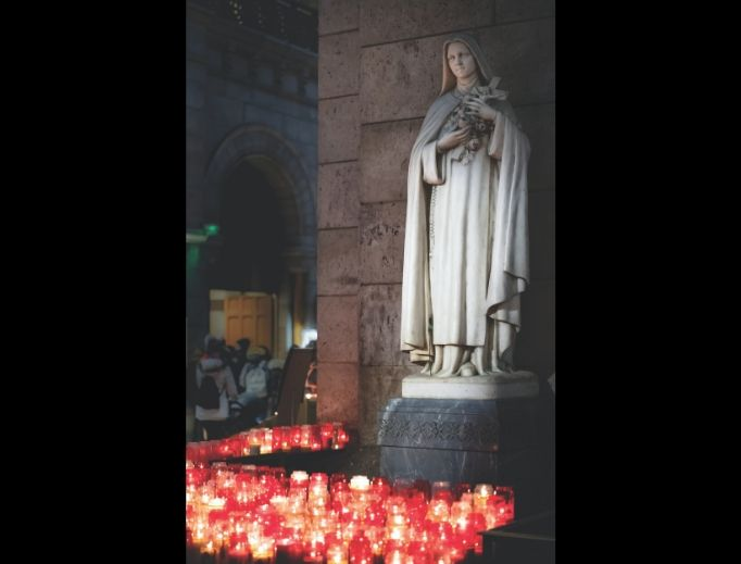 The faithful pray and light candles before a statue of St. Thérèse at Sacre Coeur Basilica in Paris.