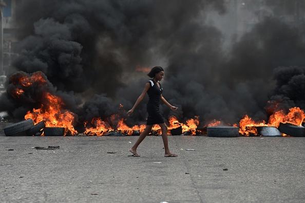 A woman walks past tire barricades set ablaze by demonstrators protesting in Port-au-Prince against Haitian President Jovenel Moise Feb. 10.