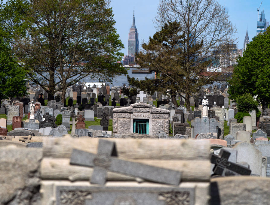 The Empire State Building is seen in the distance behind the tombstones at Calvary Cemetery on May 10, 2020, in the Queens borough of New York City, after the Archdiocese of New York lifted COVID-related cemetery-visitation restrictions for Mothers Day.