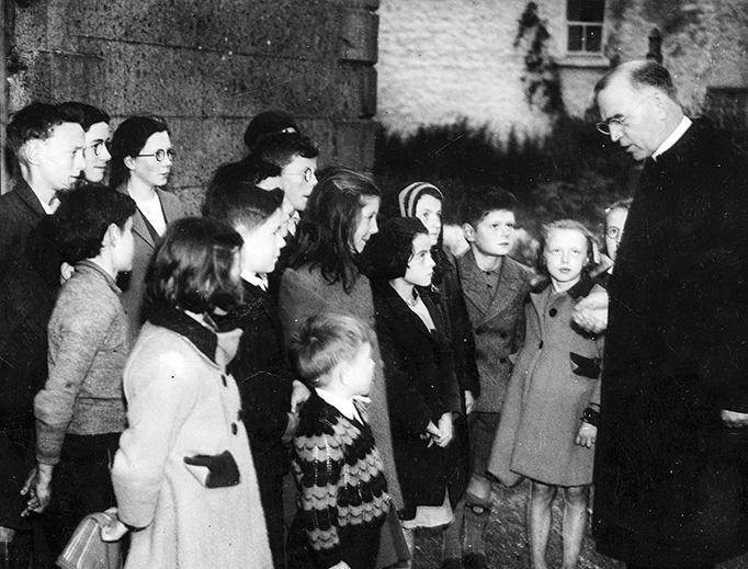 Father Flanagan talking with children in his hometown of Ballymoe, Ireland, 1946.