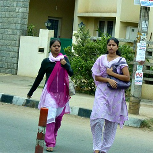 Young women walk along a street in Bangalore, India.