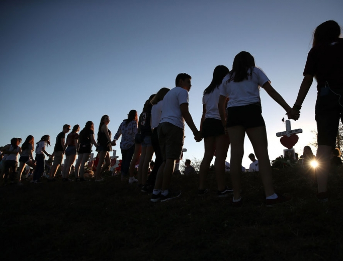 Students and family members holds hands Feb. 18 around a makeshift memorial in front of Marjory Stoneman Douglas High School, where 17 people were killed Feb. 14 in Parkland, Florida.