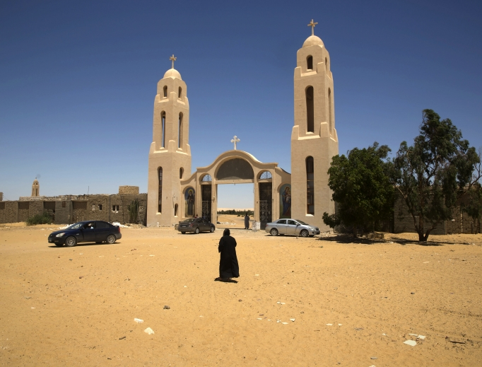 A priest walks in front of St. Samuel the Confessor Monastery, about 140 miles south of Cairo, Egypt, May 27. Masked gunmen ambushed a bus carrying Coptic Christians on their way to the monastery on Friday, killing 29 people.