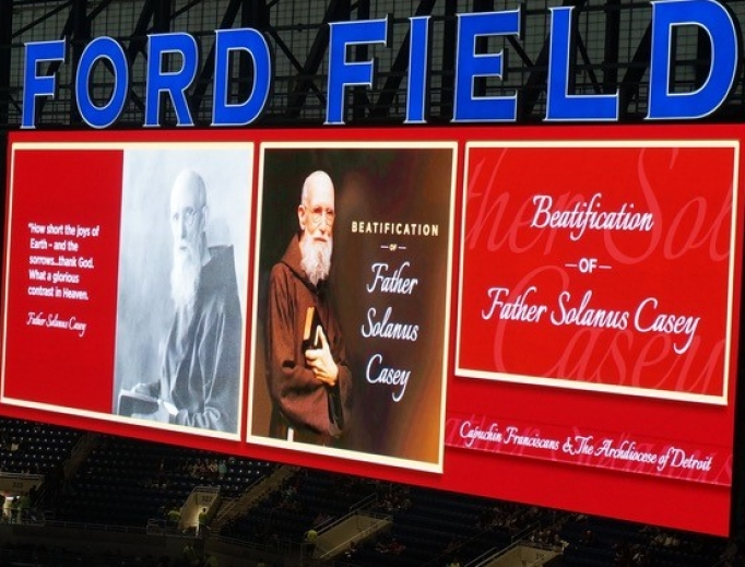 Above, the JumboTron announces the holy event at Ford Field Nov. 18; below,  the thousands in attendance, Cardinal Angelo Amato celebrating the Mass, and the official portrait of Blessed Solanus Casey seen center stage.