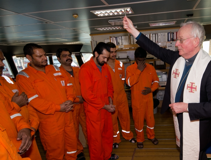 The Malaviya 7 crew is blessed by Benedictine Bishop Hugh Gilbert of Aberdeen, Scotland. The Apostleship of the Sea keeps seamen rooted to their faith on the open waters.