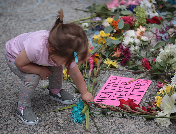 A young girl puts flowers on a memorial to Heather Heyer that was chalked on the pavement during a demonstration on August 13, 2017 in Chicago, Illinois. Heyer was killed and 19 others were injured in Charlottesville, Virginia when a car plowed into a group of activists who were preparing to march in opposition to a nearby white nationalist rally.