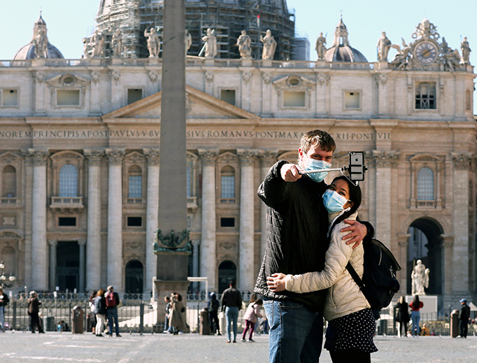 Vatican tourists wearing protective masks take a selfie Thursday in front of St. Peter's Basilica.