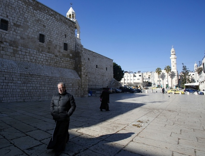 A priest walks in the Church of the Nativity compound in the occupied West Bank city of Bethlehem on March 8, after it came under lockdown two days ago as an emergency measure to limit the spread of the novel coronavirus.