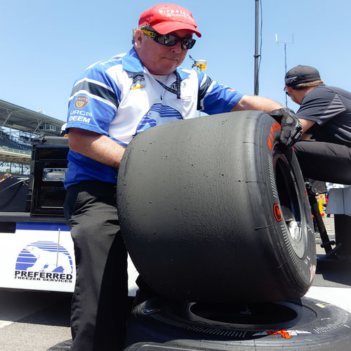 Above, Father Glenn O'Connor cleans a tire following a pit stop during practice for Josef Newgarden at the Indianapolis Motor Speedway. Below, Father O'Connor carries tires for the next session for Indianapolis 500 driver Newgarden.The priest will be working in his pits during Sunday's running of the 100th Indianapolis 500.