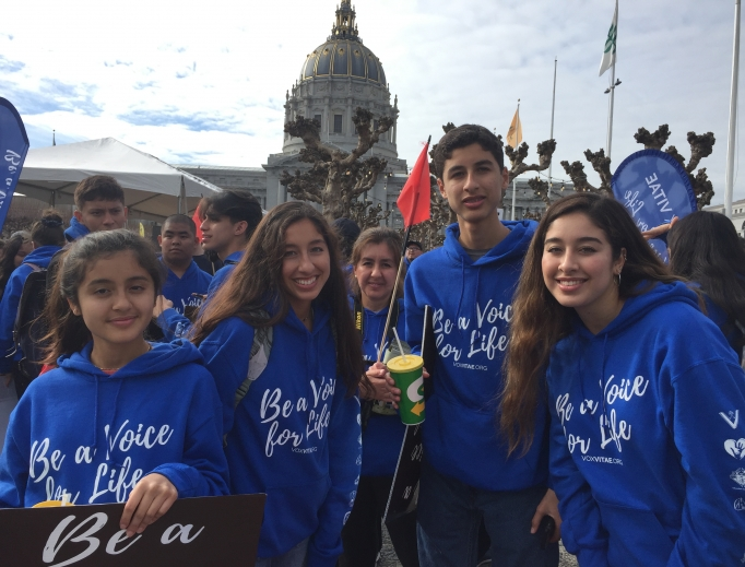 Above, teens attend the Walk for Life West Coast 2020 with Vox Vitae; below, Father Frank Pavone of Priests for Life and students from St. Joseph Academy pose for a photo in front of the San Francisco cathedral. Also below: Liz from Our Lady of Peace parish, along with her family, attends the walk, and seminarians from St. Patrick's Seminary show their support for life. Bottom of page: Yoselin Donas, r, and her family attend the 16th-annual pro-life event.