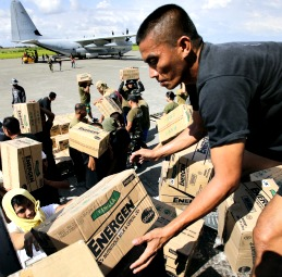 Philippine Army personnel unload relief goods to be transported to regions affected by Typhoon Bopha, from the Marine Corps KC-130J Hercules aircraft inside the International Airport in Davao, Mindanao Dec. 15.