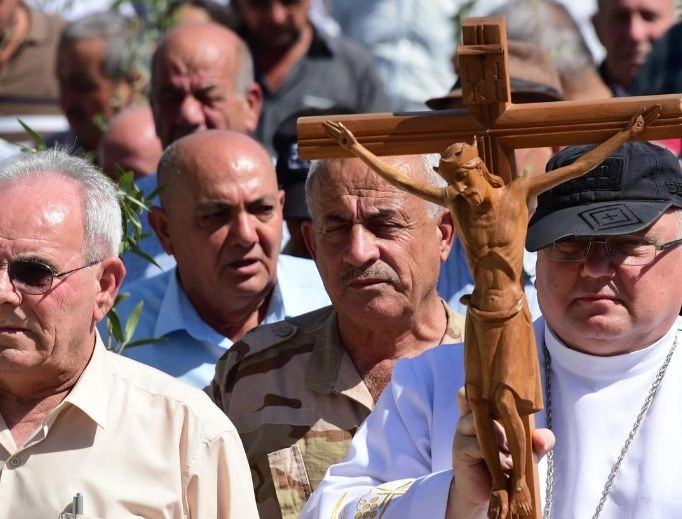 A religious procession takes place in Qaraqosh, Iraq. Father Andrzej Halemba, shown at front right holding the crucifix, is the Middle East head of Aid to the Church in Need; the aid organization says the situation is dire for Iraqi Christians.