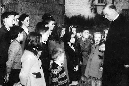 Father Flanagan talking with children in his hometown of Ballymoe, Ireland, in 1946.