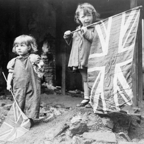 Above: Two small girls wave their flags amid rubble in the London district of Battersea on May 8, 1945. Below: A truckload of revellers celebrate on The Strand in London.