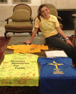 Alina Ramos poses with the four shirts she used to raise money for her trip to WYD 2013. In front of her is a daily journal she uses to document her experiences in Rio