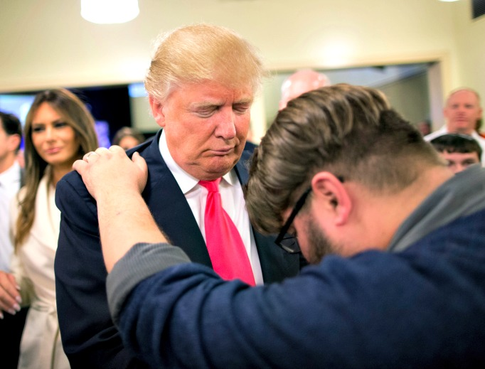 Pastor Joshua Nink prays with Republican presidential candidate Donald Trump, who was raised Presbyterian, after a service at First Christian Church on Jan. 31 in Council Bluffs, Iowa. Below, Hillary Clinton attend a service at the First United Methodist Church in Huntington, W. Va.