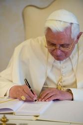 Benedict signs a copy of Caritas in Veritate.