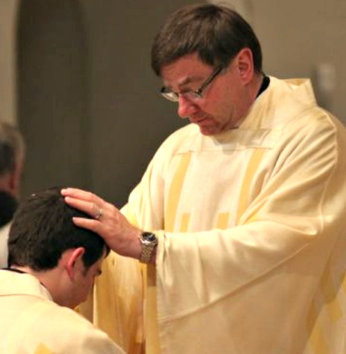 Father James Powers, who was appointed bishop of Superior on Dec. 15, blesses a newly ordained priest.