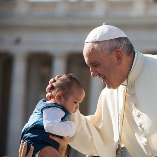 Pope Francis embraces a baby during the general audience in St. Peter's Square on Aug. 26.