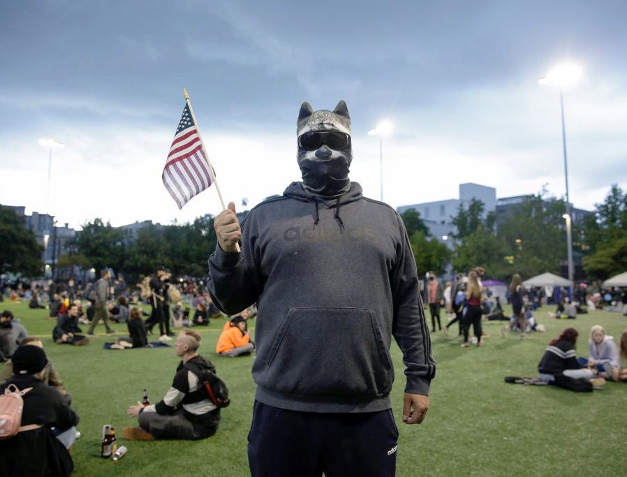 A man who wished to remain anonymous is pictured wearing a raccoon mask in an area being called the Capitol Hill Autonomous Zone (CHAZ) located around streets reopened to pedestrians after the Seattle Police Department's East Precinct was vacated in Seattle, Washington on June 12, 2020.