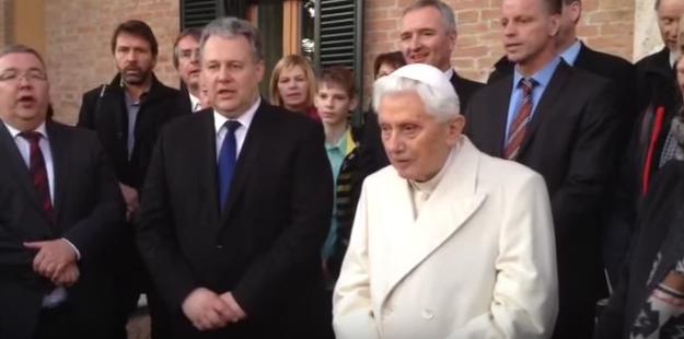 Pope Emeritus Benedict XVI and Bavarian dignitaries singing a German Christmas carol outside his residence on Friday.