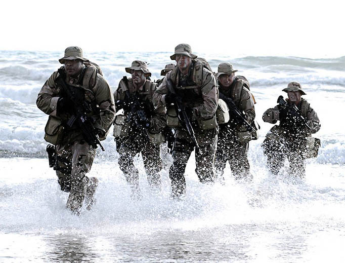 A U.S. Navy SEALs team emerges from the water