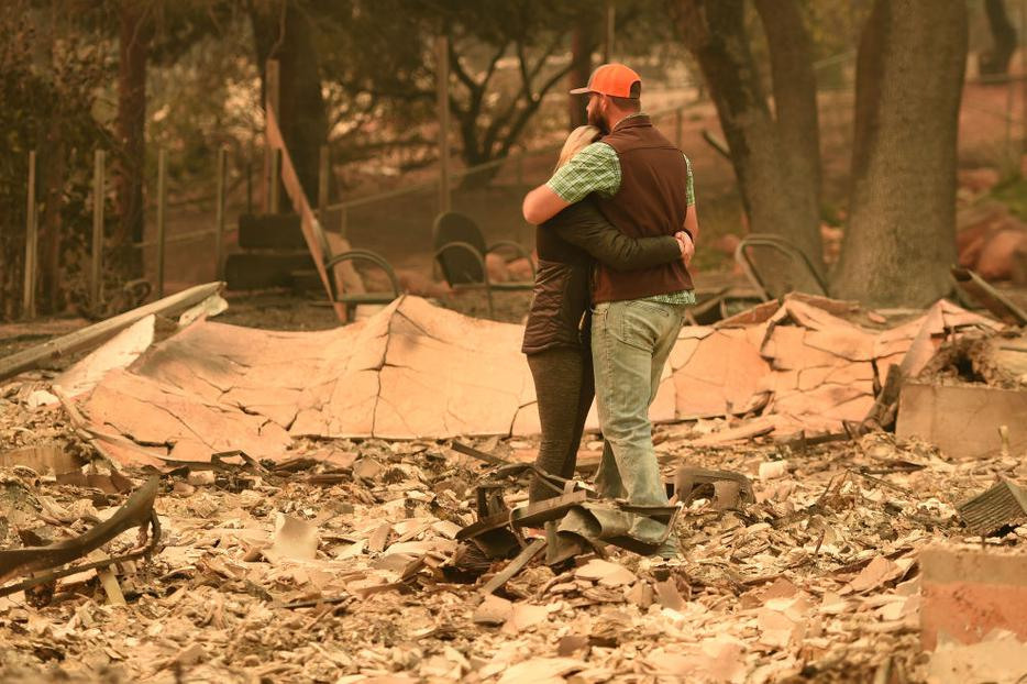 Above, Chris and Nancy Brown embrace Nov. 12 while looking over the remains of their burned residence after the Camp Fire tore through the region in Paradise, California. Below, Alameda County Sheriff Coroner officers search for human remains at a burned residence in Paradise on Nov. 12, and a welcome sign remains near a burned residence in Paradise.