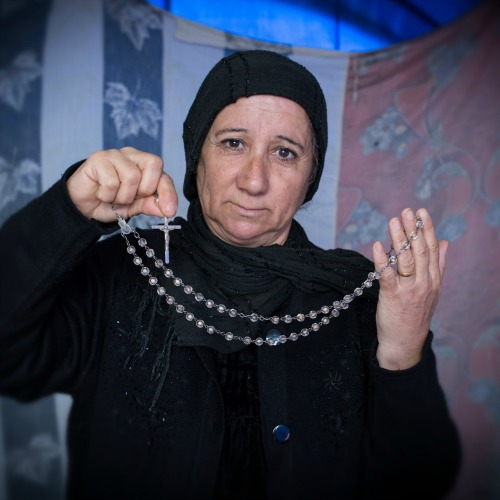 A displaced Iraqi-Christian woman from Qaraqosh displays her most prized possession last month in her tented home located on the grounds of Mar Elia Catholic Church in Erbil, Iraq.