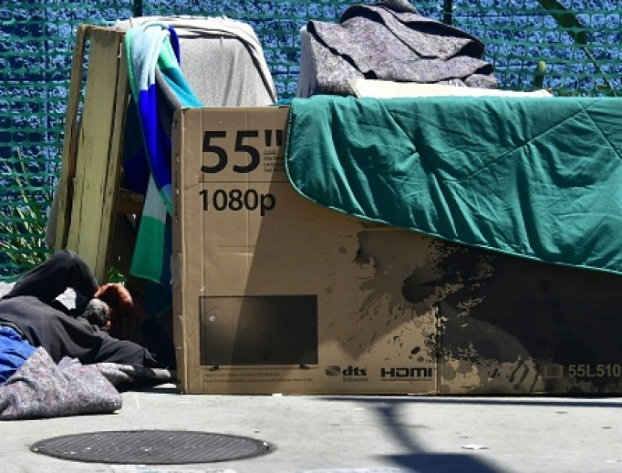 A homeless man sleeps beside his makeshift temporary shelter on a street in downtown Los Angeles June 25.