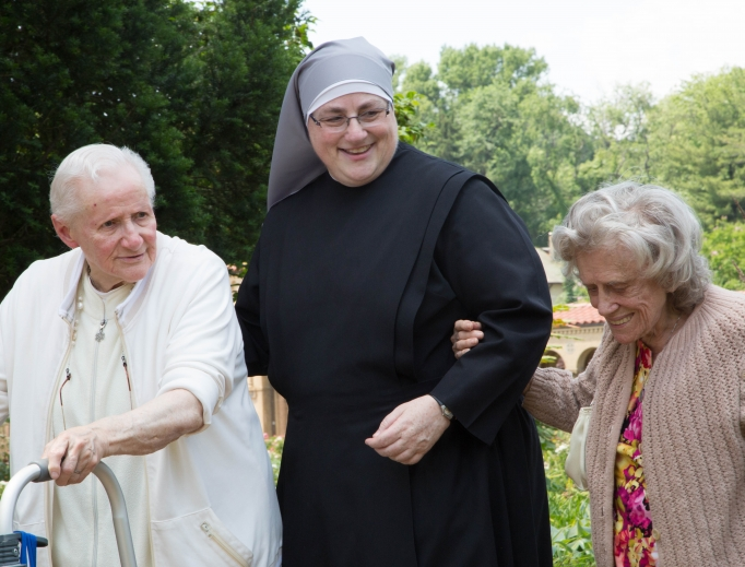 Sister Constance Veit (shown above) and other sisters interact with their dear residents in happier times; the Little Sisters of the Poor continue to provide care and fellowship according to mandated guidelines in this time of coronavirus pandemic.