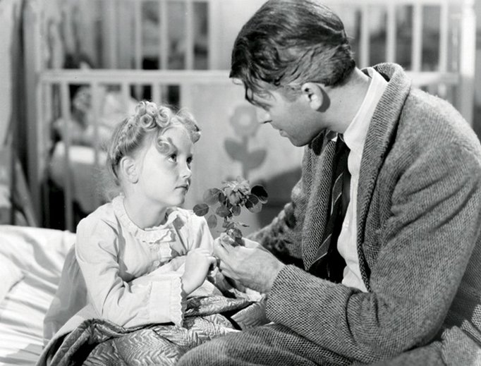 Actress Karolyn Grimes, as ZuZu Bailey, with Jimmy Stewart, as George Bailey, in It's a Wonderful Life.