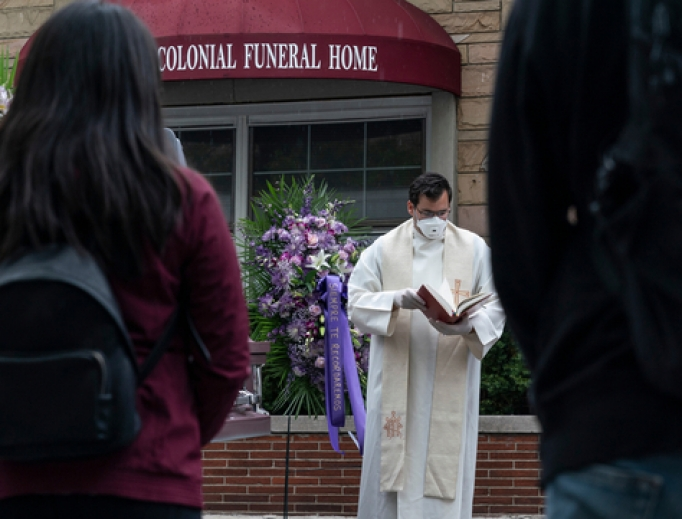 Priest prays and reads a portion of the Bible at a funeral for someone who died during the COVID-19 pandemic at Riverdale Funeral Home in Inwood Manhattan on May 8.