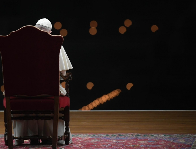 Pope Francis sits in a dark St. Peter's Square during the Way of the Cross on April 10, 2020.