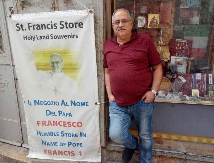 Above, Alfred Ra'ad, the Catholic owner of the St. Francis Store in the Christian Quarter of the Old City of Jerusalem, used to earn $300-$400 per day before the Jerusalem municipality built a light rail line right outside the entrance to the Christian Quarter. Today, tour buses cannot park there, and Ra'ad sometimes earns as little as $10 per day. Below, schoolchildren walk through the Christian Quarter of the Old City of Jerusalem, where the population is about 20% Christian and 80% Muslim. The number of Christians in the Holy Land, now less than 2% of the population, continues to dwindle.
