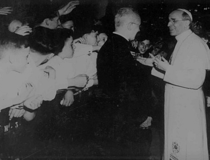 Pope Pius XII greets pilgrims during a general audience in St. Peter's Basilica.