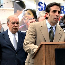 Bobby Schindler, with his father and a photo of his sister behind him, speaks at a rally.
