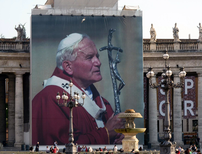 A giant image of Pope St. John Paul II hangs from the colonnade in St. Peter's Square.