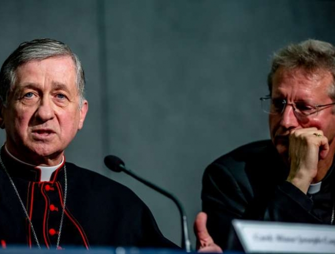 Cardinal Cupich (l) addresses the media Oct. 20 during a break at the synod on youth. He referred to the John Jay Report on the sex abuse scandal, which he said shows that the root of priestly sexual abuse is not homosexuality, but many different causes.