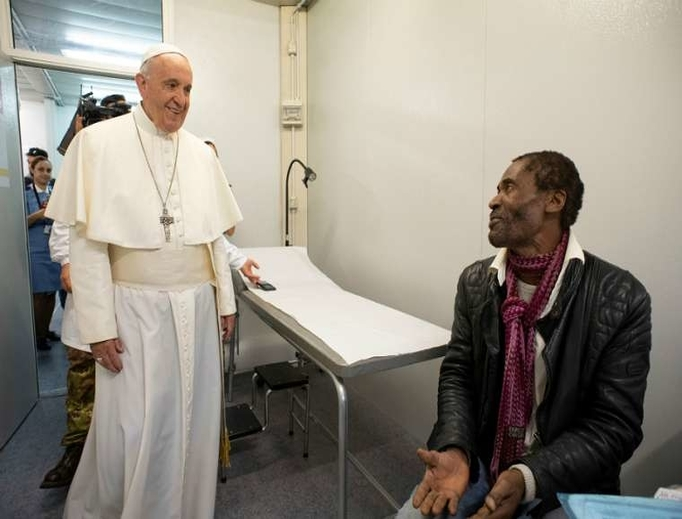 Pope Francis visits with a patient inside a clinic for the poor in Rome, 2019.