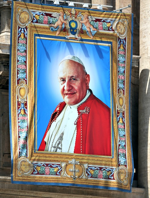 The tapestry depicting Blessed Pope John XXIII hangs on the balcony of St. Peter's Basilica on April 25.