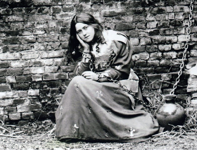 """A young French girl poses in a costume of Joan of Arc in the 1880s. About 35 years after this picture was taken, Joan of Arc was declared a saint — and five years after that, the girl in this picture was herself canonized as St. Thérèse of Lisieux, """"the Little Flower."""""""