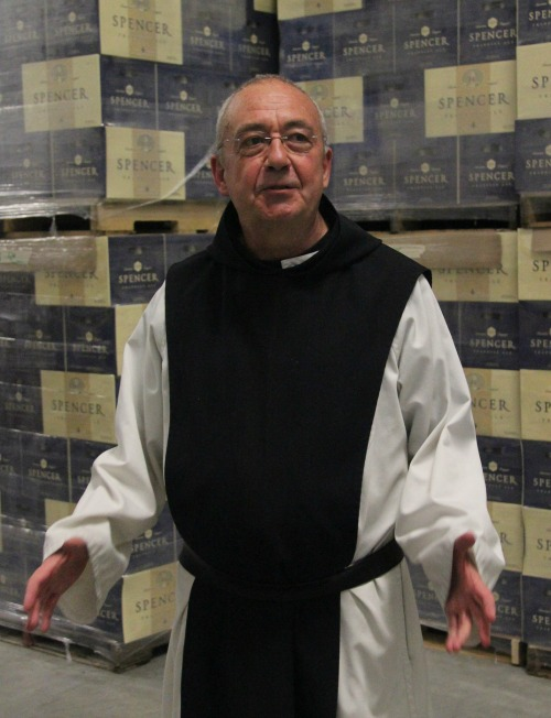 Spencer Brewery director Father Isaac stands in front of cases of Spencer Trappist Ale, the first certified Trappist beer made outside of Europe.