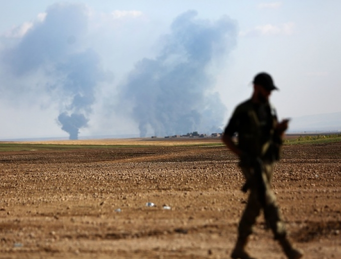 A Turkey-backed Syrian fighter walks as smoke billows in the distance during clashes between Syrian regime forces and Turkish forces near the northeastern town of Ras al-Ein on Oct. 30.