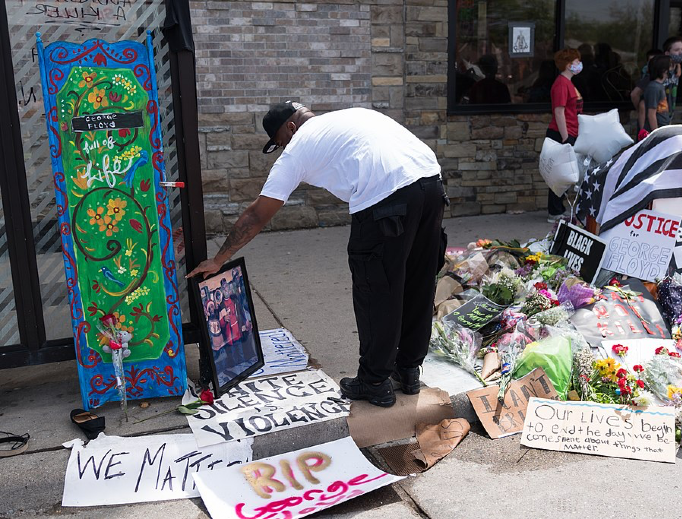 A man leaves a photograph at a memorial for George Floyd on May 27 in Minneapolis.