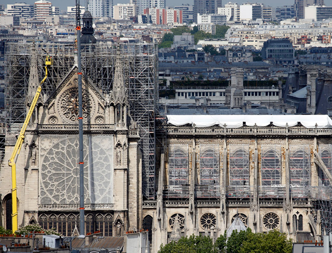 Temporary tarpaulins cover the roof of the Notre-Dame cathedral to protect it from the rain damage following the massive fire earlier this month, on April 29, 2019 in Paris, France. More than 1,000 conservators, architects and professors from France and abroad have spoken out against President Macron's promise to rebuild Notre Dame within five years, citing fears that a hasty restoration would be irresponsible.