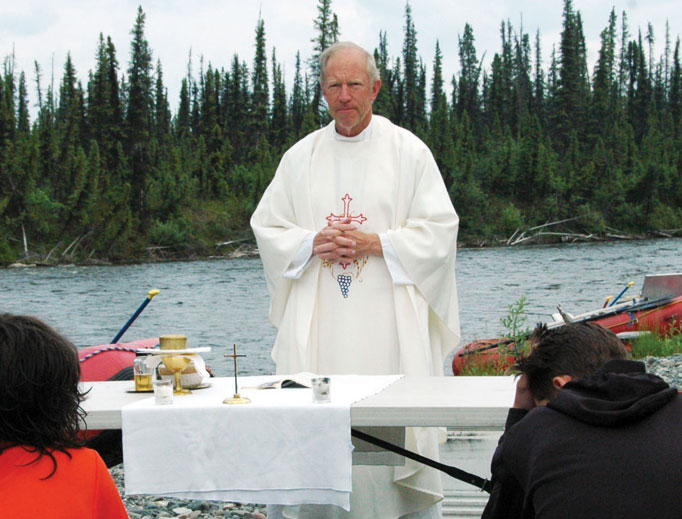 Above, Father Kermit Syren, founder of Camp Kodiak, celebrates Mass last summer on the banks of Alaska's Gulkana River. Daily Mass is part of the morning tradition at 'Camp Kodiak' high-adventure camp. Below, Camp Kodiak participants pray during an outdoor Stations of the Cross at the entrance of the Wrangell St. Elias National Park in Alaska.