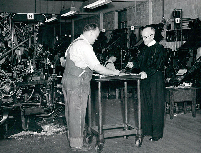 National Catholic Register founding editor Msgr. Matthew Smith (R) reviews an issue in the Register's mid-century print facility.