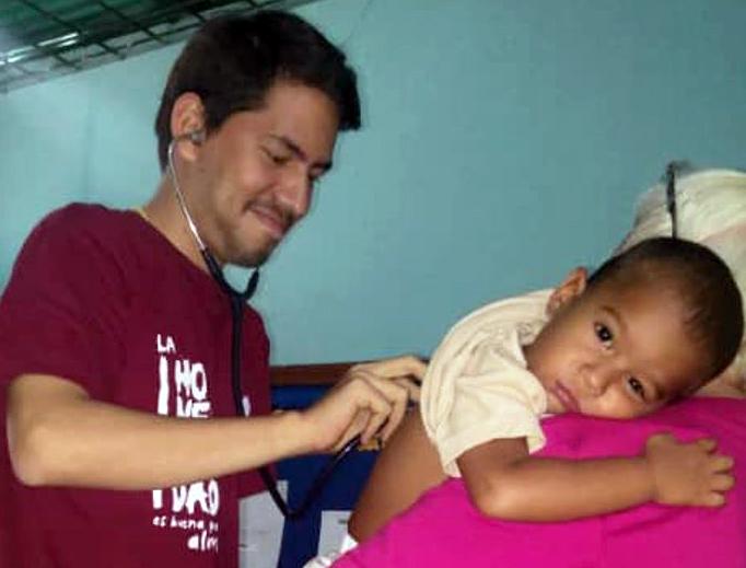 Dr. Lenin Mejías Peña checks up on a young patient in Venezuela.