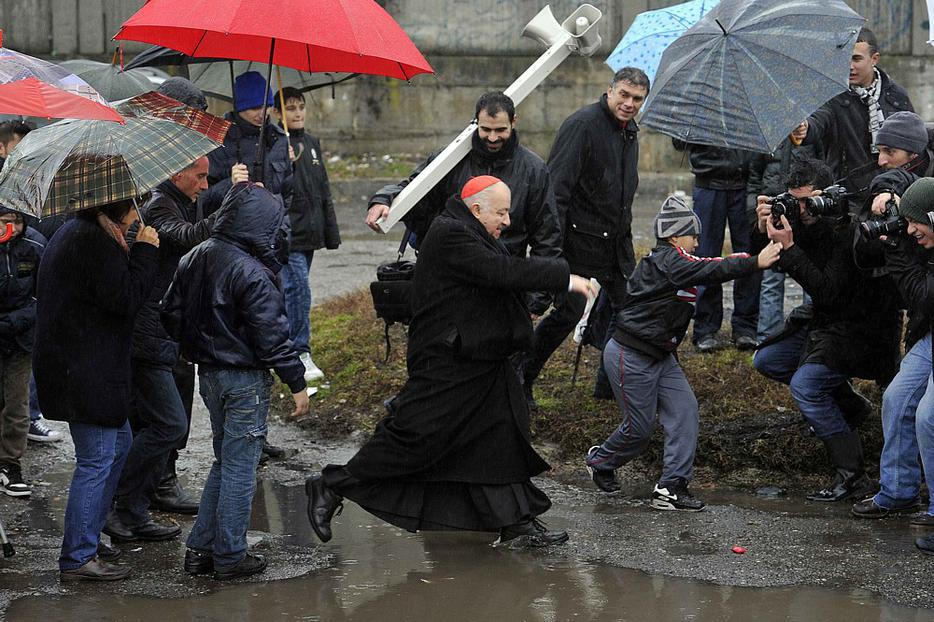 Italian Cardinal Dionigi Tettamanzi of Milan jumps over a puddle during a visit to a Gypsy, or Roma, camp in a Milan neighborhood Dec. 23. 2010.